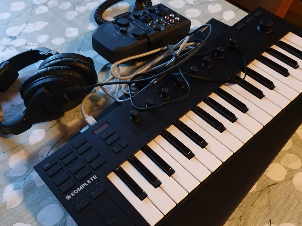 A laptop, a compact audio interface, a headset and a mini keyboard